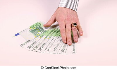 Man's hand spread the 100 Euro banknotes on the table -...