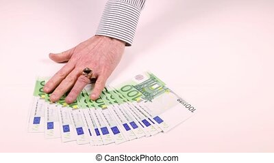Man's hand spread the one hundred Euro banknotes on the table