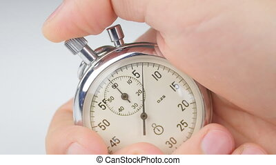 man's hand starting up a stopwatch at white background - ...
