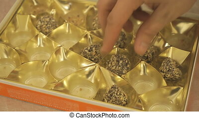 Man's hand taking a chocolate truffle from a box
