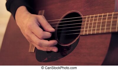 Man's hand touches on strings of acoustic guitar by mediator. Close up.