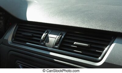Man's hand twist switch of air conditioning in the car....