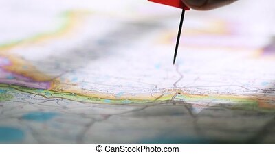 Man's hand with a flag pin on the map is showing destination...