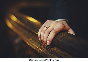 Man's hand with an engagement ring holds old wooden list