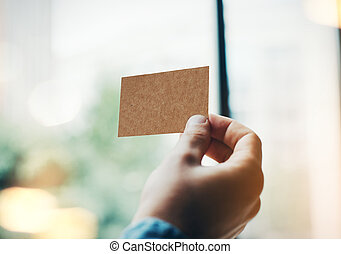 Man's hand with craft business card on the blurred background wi