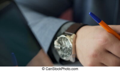 Man's hand with expensive watches on his wrist writes pen on...