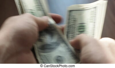 Man's hands counting hundred dollar bills