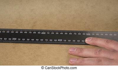Man's hands draw a pencil line