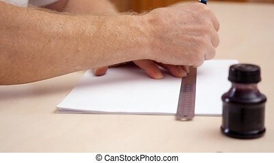 Mans hands drawing a line on white blank with ruler and...