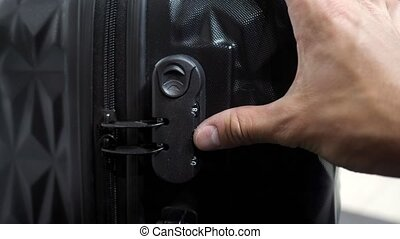 Man is testing lock. He enters the code to open suitcase combination lock on the suitcase and presses the button, hands closeup.