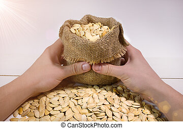 Man's hands holding a sack with a pumpkin seed with flare