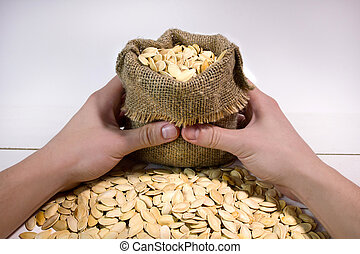 Man's hands holding a sack with pumpkin seed