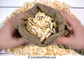 Man's hands holding a sack with pumpkin seed, top view