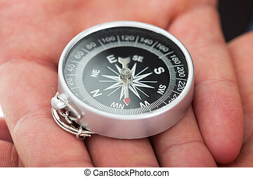 Man's Hands Holding Compass