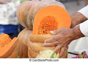Mans hands holding pumpkin at market stall.