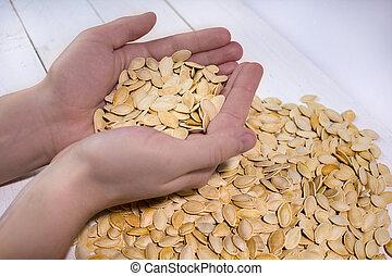 Man's hands holding pumpkin seed