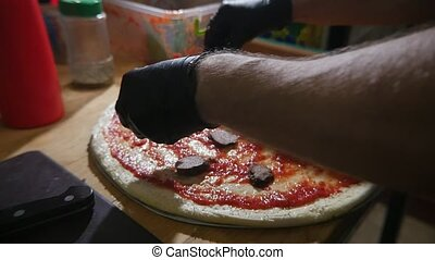 Man`s hands in gloves making pizza and spreading salami on dough in slo-mo