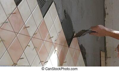 Installing Ceramic Tile - Man's hands Installing Ceramic...