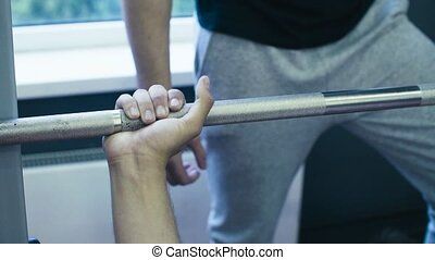 Man's hands lifting barbell
