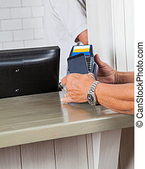 Man's Hands Making Payment Through Cellphone At Counter