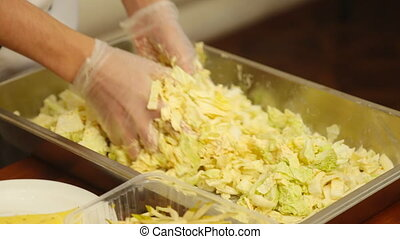 Hands mixed salad in a factory