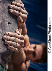 man's hands on handhold on artificial climbing wall