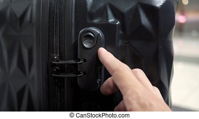 man enters the code to open suitcase combination lock on the suitcase and presses the button, hands closeup.