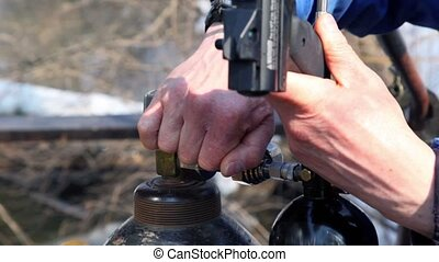 Mans hands operate with gas cylinder and paintball gun