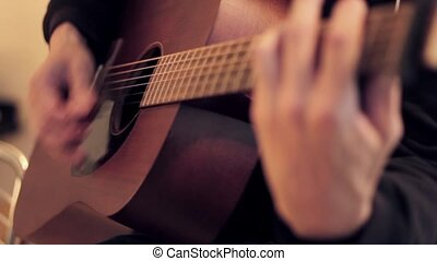 Man's hands playing acoustic guitar by mediator. Fretboard...