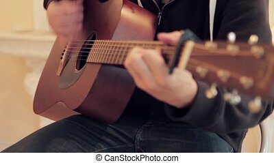 Man's hands playing acoustic guitar by mediator.