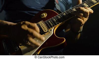 Man's hands playing electric guitar, - Closeup of man's...