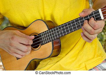 Man's hands playing ukulele