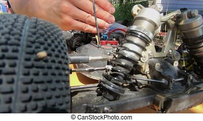 Man's hands screwing screw in a remote buggy car. Close up ...