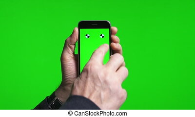 Man's hands scrolling pages using phone with green screen -...