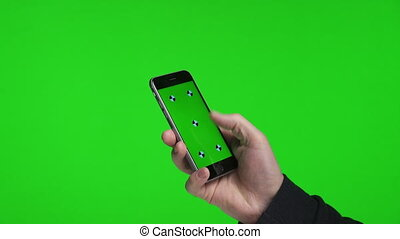 Man's hands scrolling pages using phone with green screen...