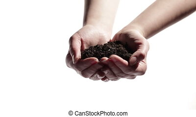 Man's hands support woman's hands with soil.