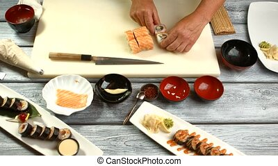 Man's hands touching sushi.