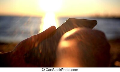 man's hands uses mobile smartphone near the sea at sunset beach. With blurred reflected In water background