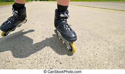 Mans legs roller skating on the asphal. Close up view to quick movement of black inline boots.