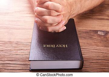 Man's Praying Hands On Bible