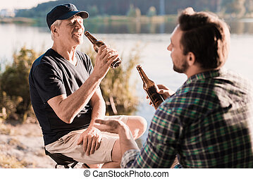 Man's rest. A man drinks beer on a fishing trip with his elderly father. They are sitting on the river bank