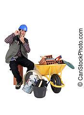 Mans sat making call next to wheelbarrow full of bricks