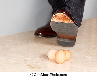 Man's shoe stamping on three eggs
