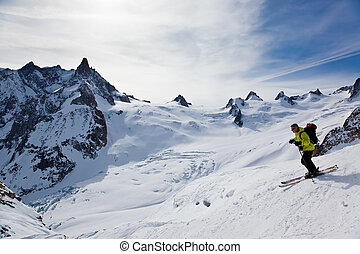 Man\'s skiing - Male skier moving down in snow powder;...