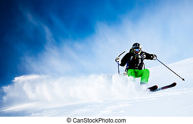 Young male freeride skier over blue sky turning in powder snow; black jacket; green pant; horizontal orientation