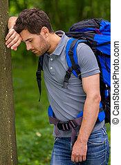 mantendo, cansadas, mochila, árvore, jovem, traveler., fechado, inclinar-se, vista, olhos, lado, homem
