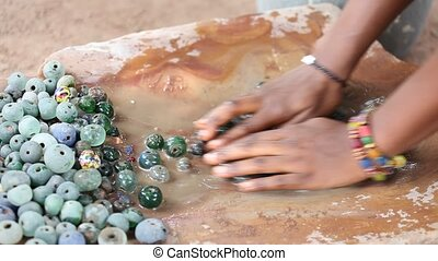 Manual cleaning of glass beads in the manufacture, Ghana,...
