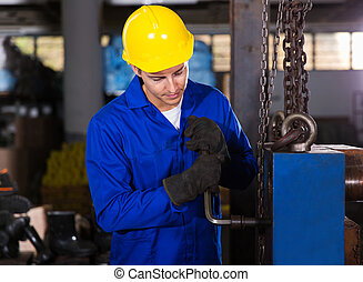 factory worker adjusting machine