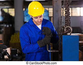 factory worker adjusting machine - manual factory worker...