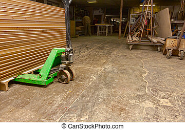 Manual forklift loaded with wooden, glued profiles in warehouse of carpentry